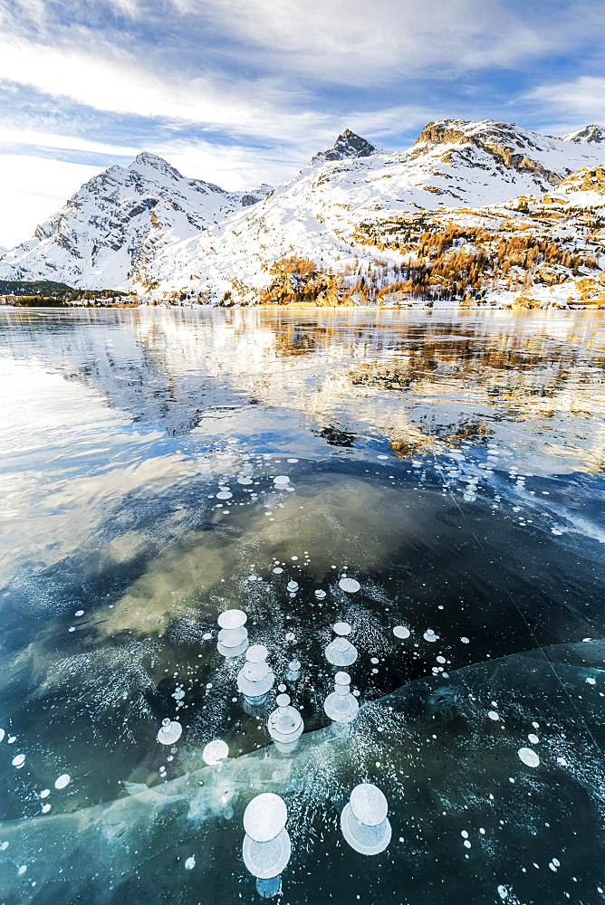 Methane bubbles in the icy surface of Silsersee with snowy peak, Lake Sils, Engadine Valley, Graubunden, Swiss Alps, Switzerland, Europe