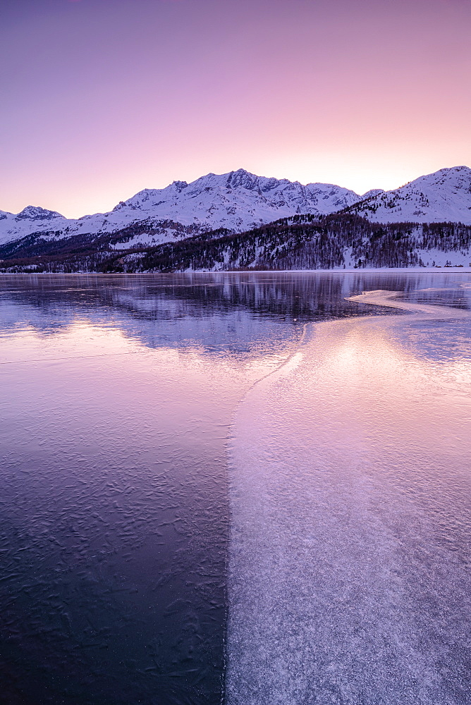 Colors of sunrise is reflected on the icy surface of Lake Sils, Engadine Valley, Graubunden, Swiss Alps, Switzerland, Europe
