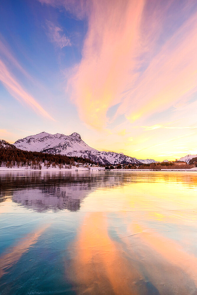 Colors of sunset is reflected on the icy surface of Lake Sils, Engadin Valley, Graubunden, Switzerland, Europe.