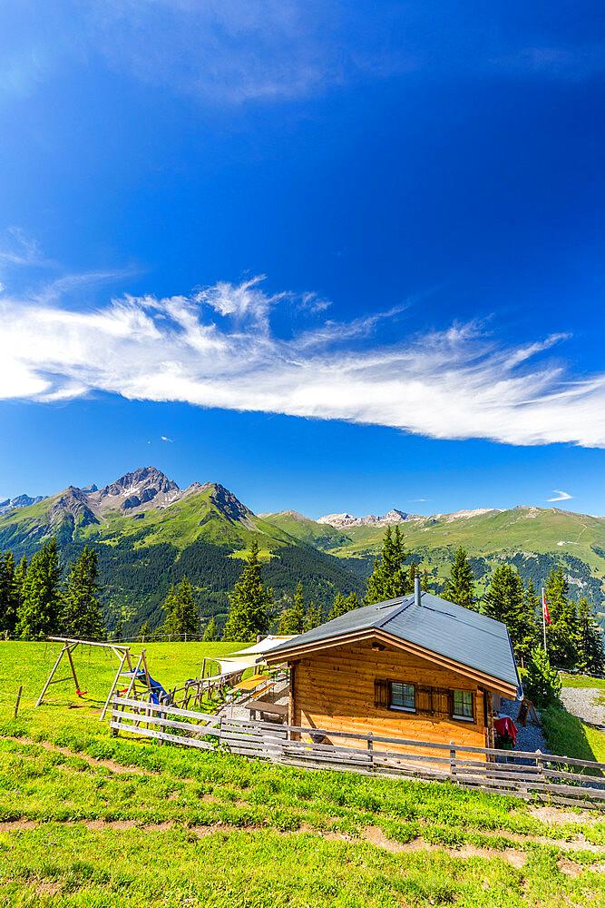 Alpine hut with Swiss flag, beneath stunning clouds. Surses, Surselva, Graubunden, Switzerland, Europe