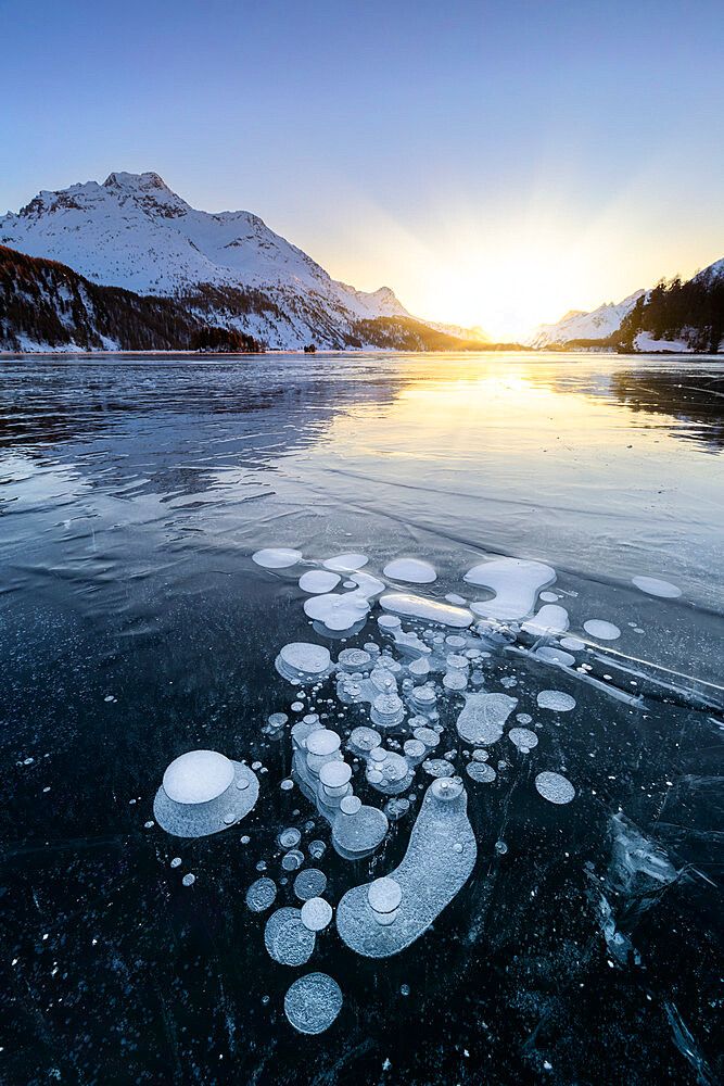 Methane bubbles in the icy surface of Silsersee with snowy peak illuminated by sunset light, Lake Sils, Engadine Valley, canton of Graubunden, Switzerland, Europe - 1269-675