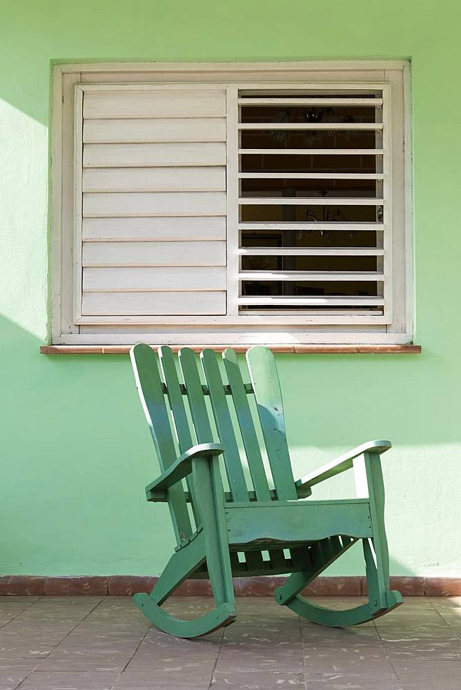 Green rocking chair on veranda UNESCO World Heritage Site, Vinales, Pinar del Rio, Cuba, West Indies, Caribbean, Central America