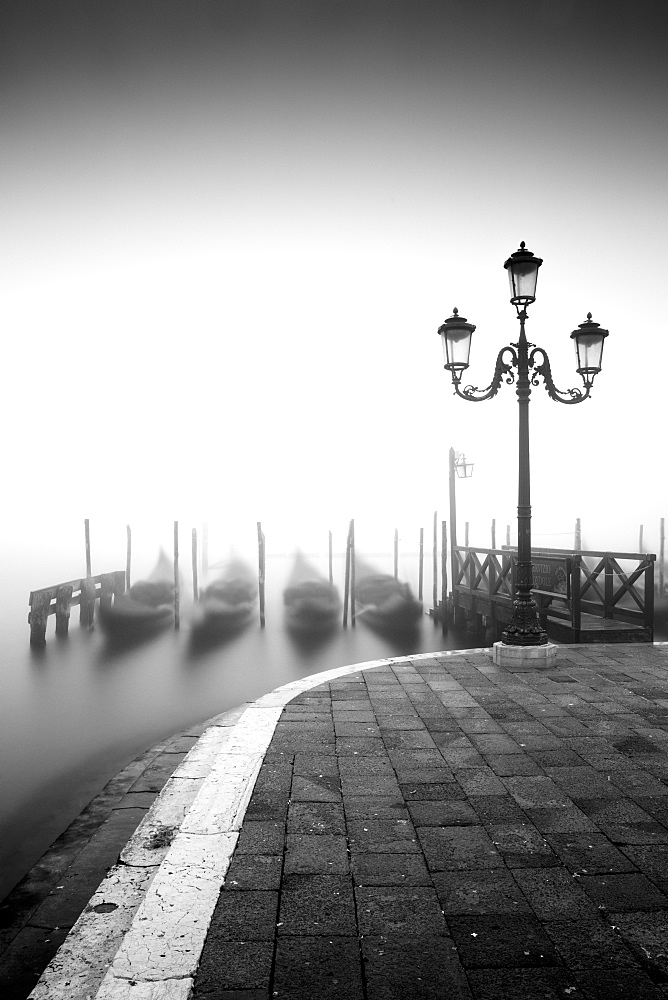 Black and white gondolas and lamp in the mist, St. Mark's Square, with Grand Canal in the background, Venice, UNESCO World Heritage Site, Veneto, Italy, Europe