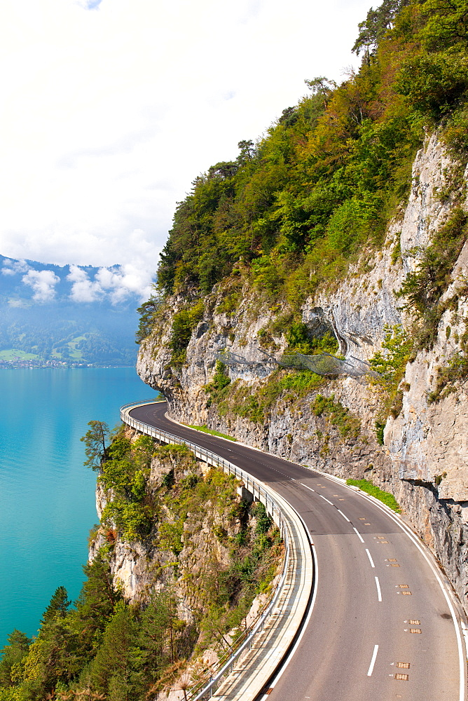 A curved road built into the side of a mountain next to Lake Thun, Interlaken, Bernese Oberland, Bern, Switzerland, Europe - 1284-181
