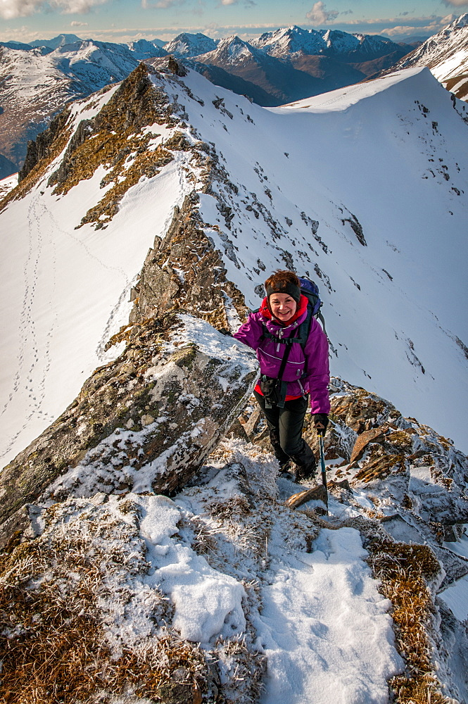 A mature female hill walker on the Brothers Ridge above Glen Shiel, Kintail in winter, Highlands, Scotland, United Kingdom, Europe