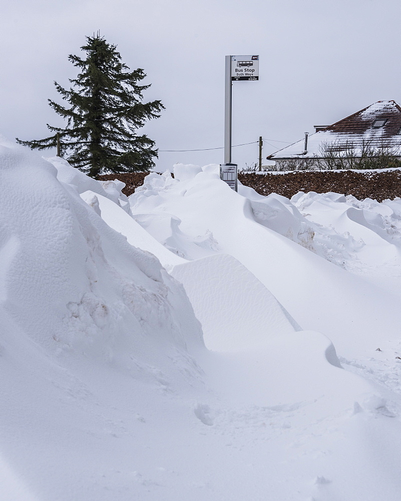 Snow drifts at a bus stop on the edge of Lennoxtown, at the foot of the Campsie Fells, East Dunbartonshire, Scotland, United Kingdom, Europe