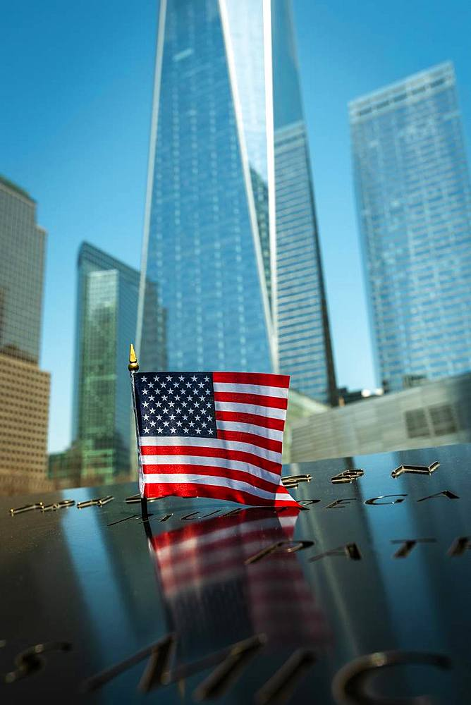 A small American flag at the 9/11 Memorial Park in New York City with the new World Trade Centre rising in the background, New York, United States of America, North America