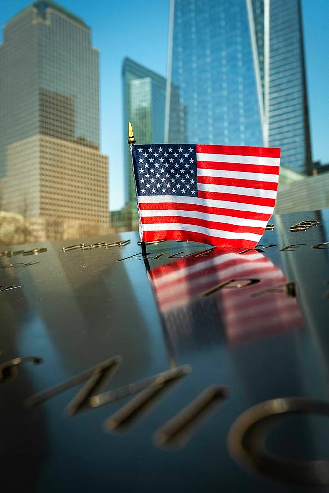 A small American flag at the 9/11 Memorial Park in New York City with the new World Trade Centre rising in the background, New York, United States of America, North America - 1287-71