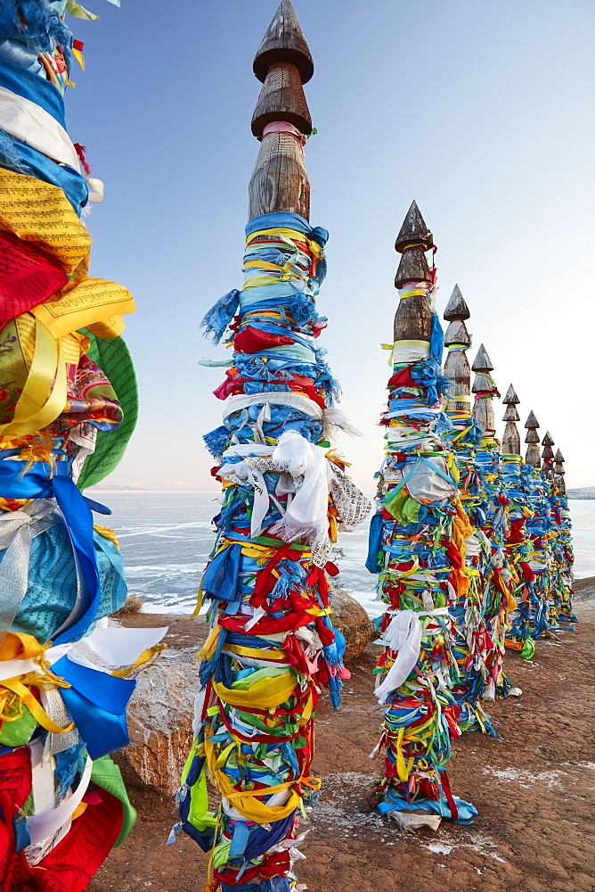 Colorful decorated Buddhist shaman poles above Lake Baikal on Olkhon island at sunrise in winter, Siberia, Russia, Eurasia