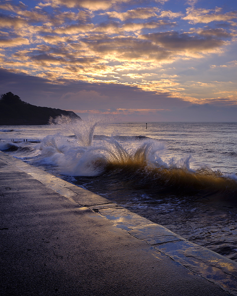 Waves backlit by the dawn sun reflect off the sea wall and impact with an incoming one, Exmouth, Devon, England, United Kingdom, Europe