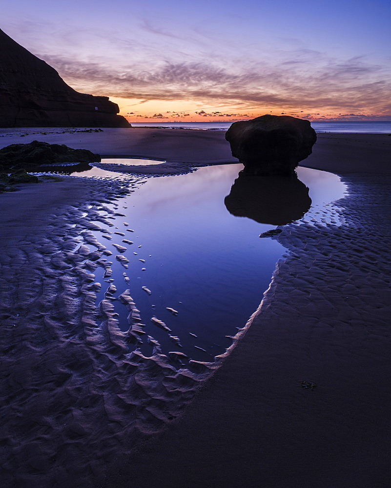 Dawn twilight with clouds reflected in a pool on the beach at Orcombe Point, Exmouth, Devon, UK.