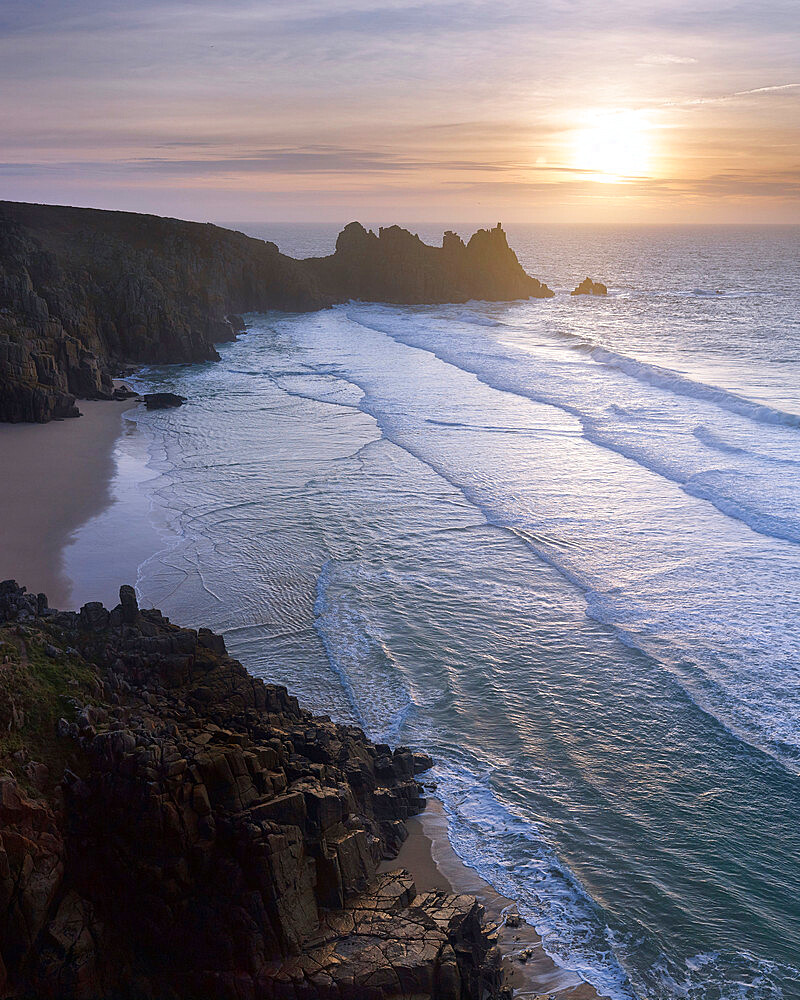 Sunrise over the beautiful & secluded beach at Pedn Vounder overlooking Logan Rock, near Porthcurno, Cornwall, UK