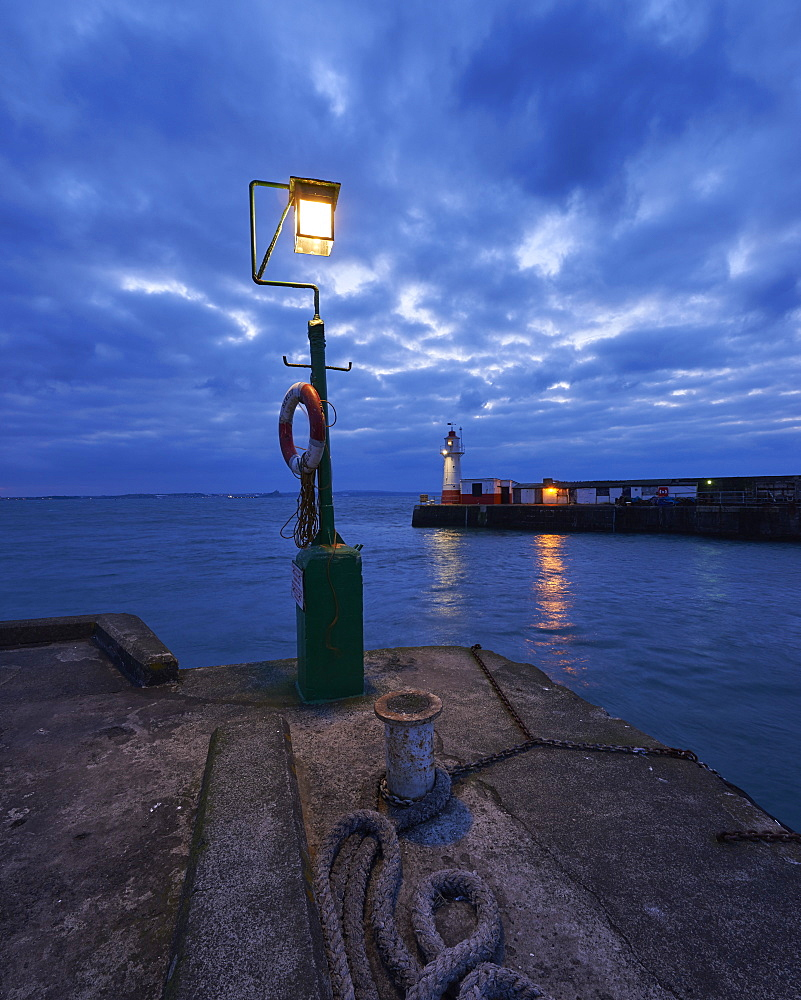 Lights at end of harbour walls in twilight, Newlyn, Cornwall, UK