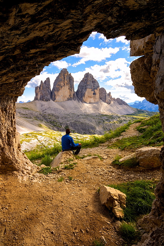 Hiker admires the three peaks of Lavaredo from the caves, Natural Park of the Three Peaks, Trentino-Alto Adige, Italy, Europe - 1299-49