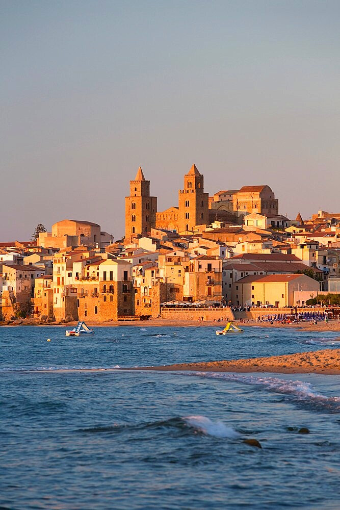 View from beach along water's edge to the town and UNESCO listed Arab-Norman cathedral, sunset, Cefalu, Palermo, Sicily, Italy - 1310-153