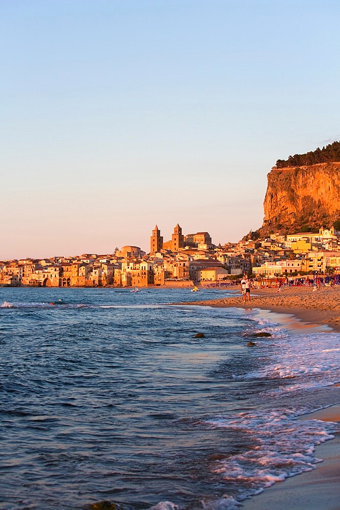 View from beach along water's edge to the town and UNESCO listed Arab-Norman cathedral, sunset, Cefalu, Palermo, Sicily, Italy - 1310-154