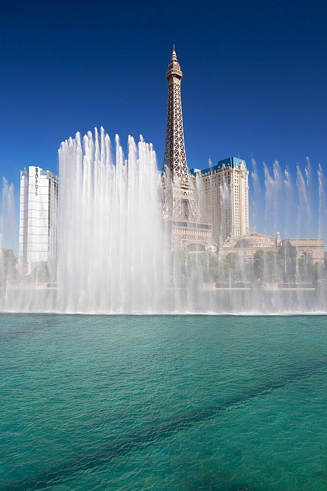 View across lake to replica Eiffel Tower at the Paris Hotel and Casino, Bellagio fountains in foreground, Las Vegas, Nevada, United States of America, North America - 1310-197
