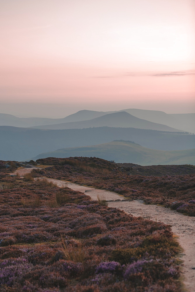 A path in the Peak District National Park leading towards the mountains in the background with a lovely pink sky, Peak District, Derbyshire, England, United Kingdom, Europe