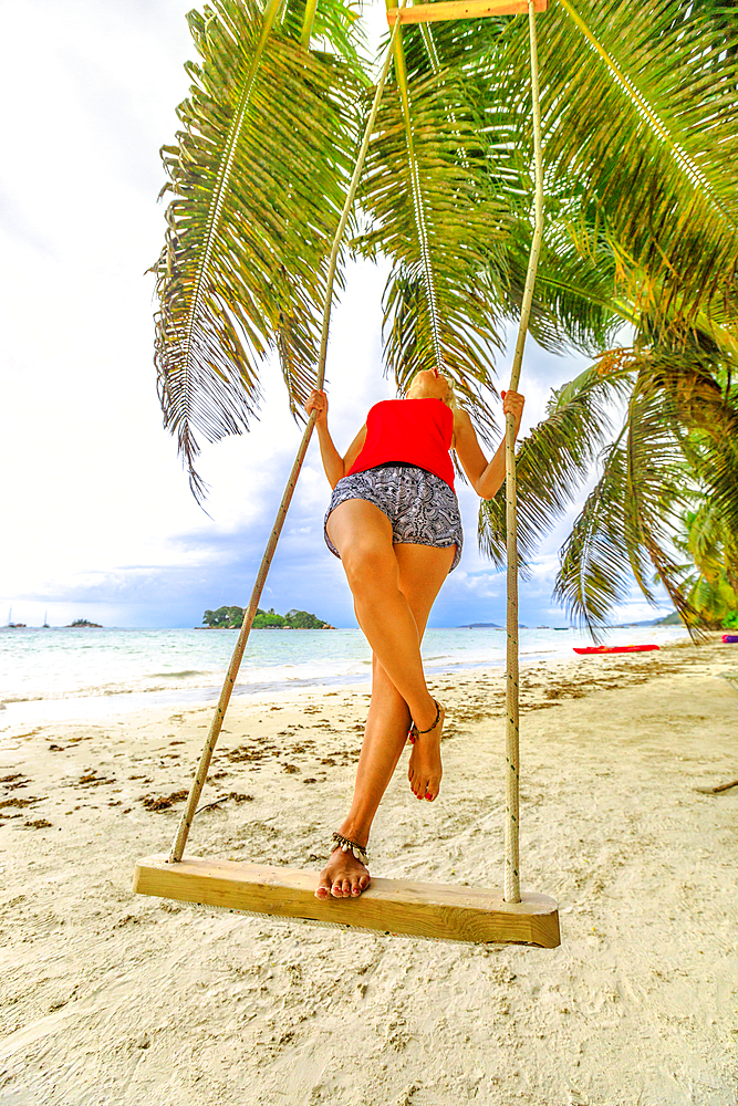 Summer vacation concept. Lifestyle tourist woman swinging on tropical beach under coconut palm trees of Anse Volbert Cote d'Or, Praslin, Seychelles, Indian Ocean. Islet of Chauve Souris on background.
