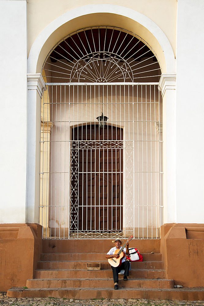 Man performing with his guitar on the steps of a church in Plaza Mayor, Trinidad, UNESCO World Heritage Site, Cuba, West Indies, Caribbean, Central America - 1315-106