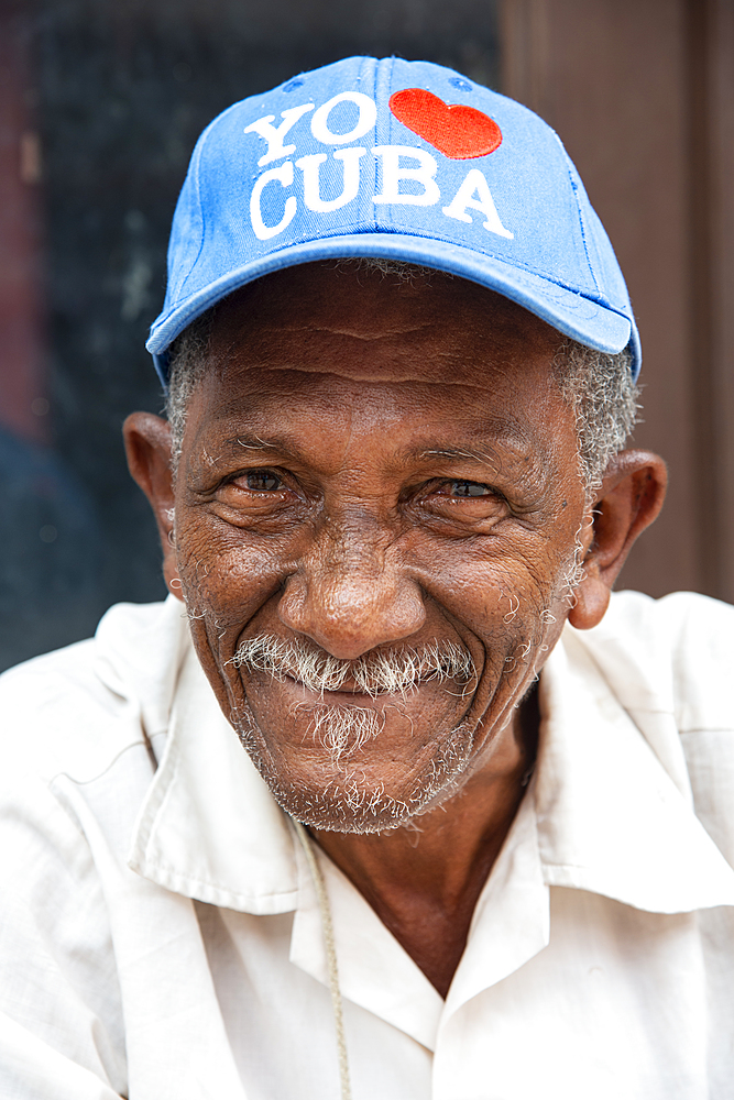 Local man wearing an 'I love Cuba' hat relaxing on the street in Trinidad, Cuba.