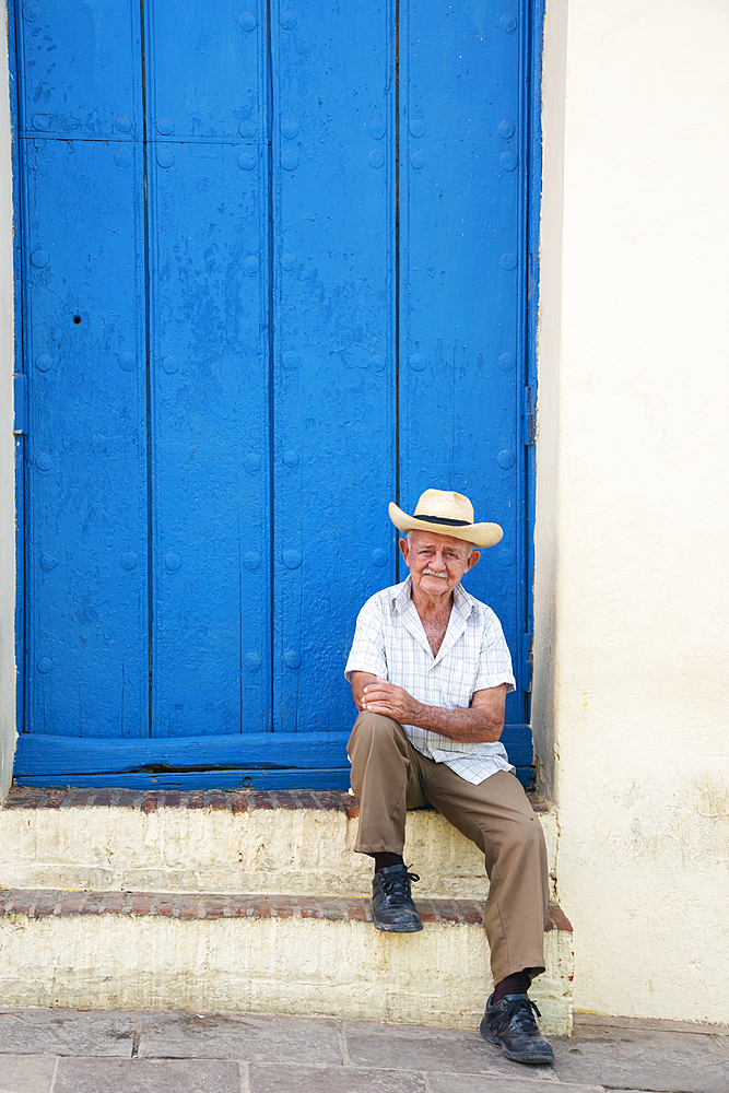 Local man relaxing along the street in Trinidad, Cuba. Model released