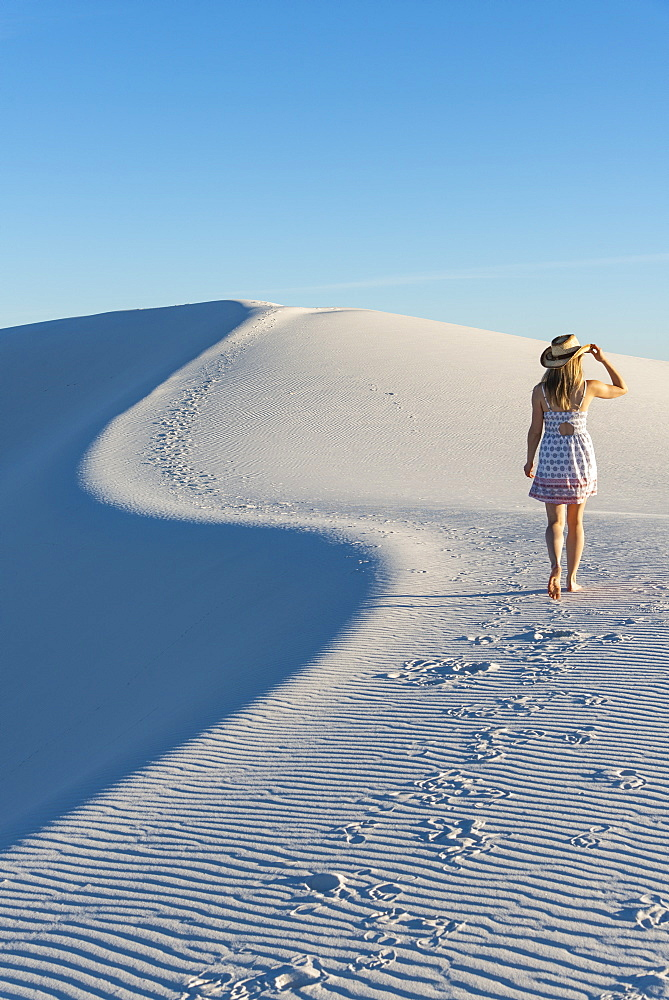 A woman walking along the S curve of a dune's ridge in White Sands National Park, New Mexico