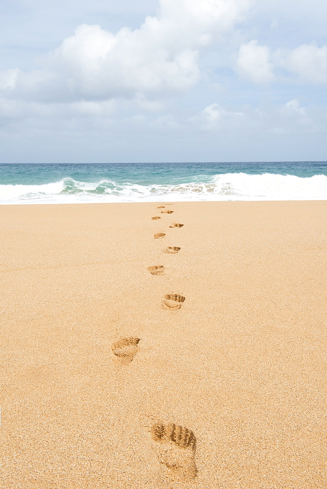 Footsteps on the beach leading into the ocean in the Hawaiian island of Kauai.