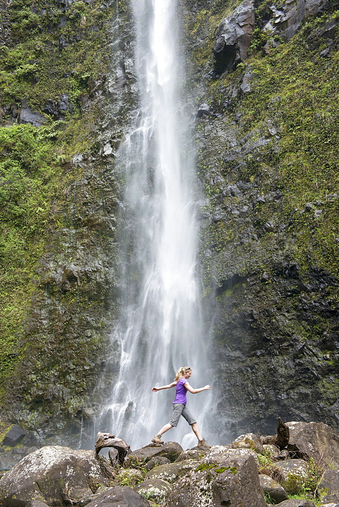 Hiker leaping in front of a waterfall along the famous Kalalau Trail, along Kauai's Na Pali Coast, Kauai, Hawaii, United States of America, North America - 1315-265
