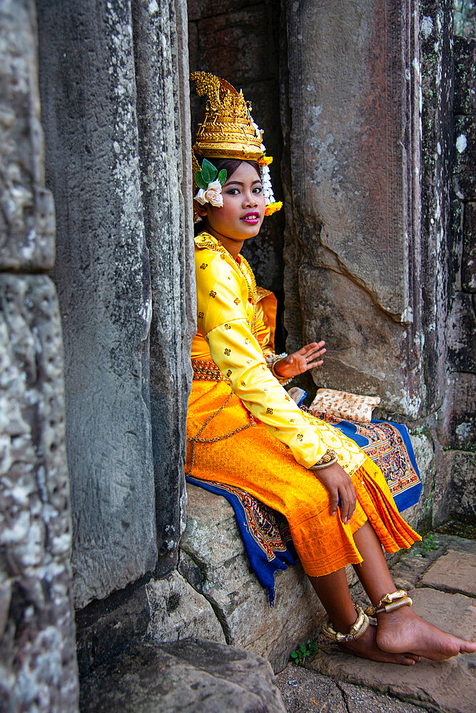 A performer taking a break among the ruins of the Angkor archaeological complex, Siem Reap, Cambodia, Indochina, Southeast Asia, Asia