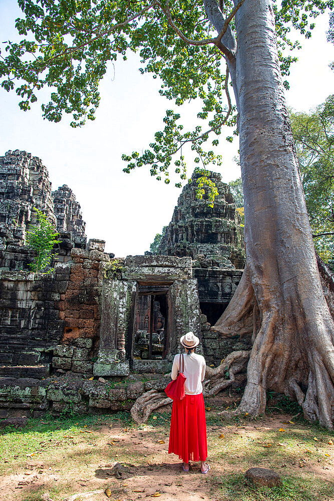 A female tourist stands in front of ruins at the Angkor archaeological complex, UNESCO World Heritage Site, Siem Reap, Cambodia, Indochina, Southeast Asia, Asia - 1315-300