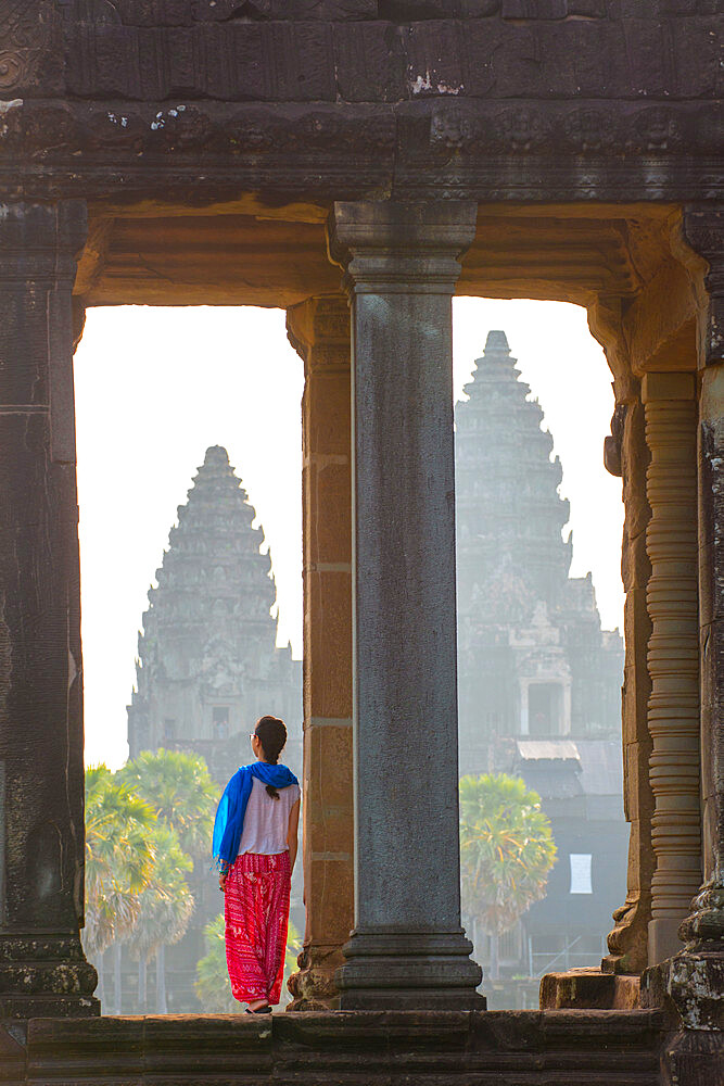 A tourist gazing out at Angkor archeological complex, UNESCO Heritage Site, Siem Reap, Cambodia