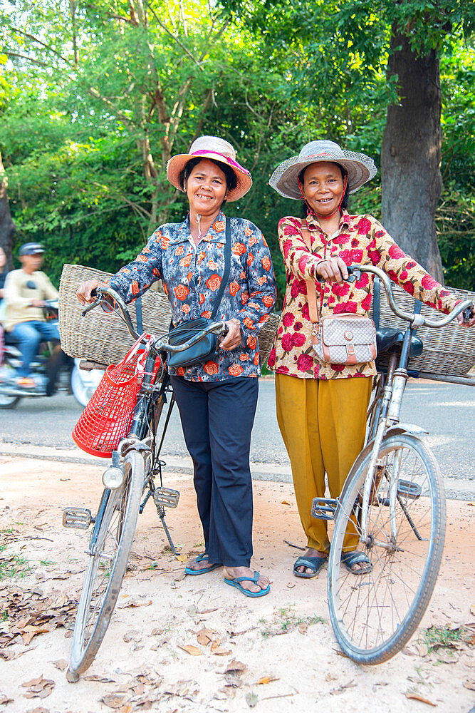 Two local women with their bicycles smiling together in Siem Reap, Cambodia, Indochina, Southeast Asia, Asia