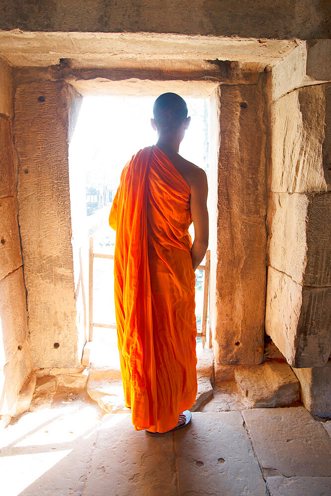A buddhist monk exploring the Angkor Archeological Complex, a UNESCO Heritage Site, in Siem Reap, Cambodia