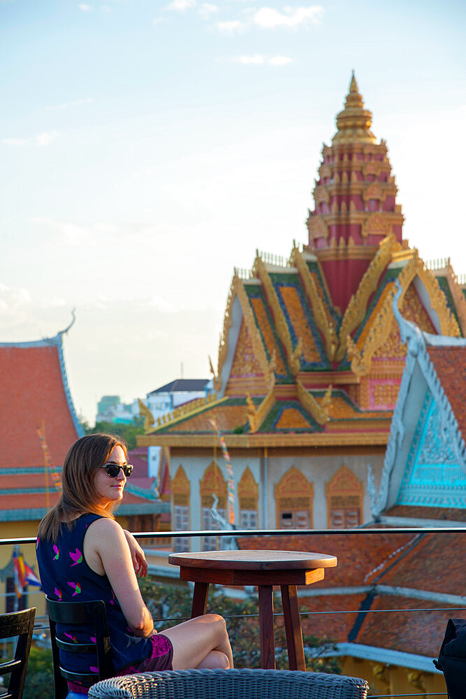 A female tourist sitting at a rooftop restaurant overlooking a temple in Phnom Penh, Cambodia, Indochina, Southeast Asia, Asia