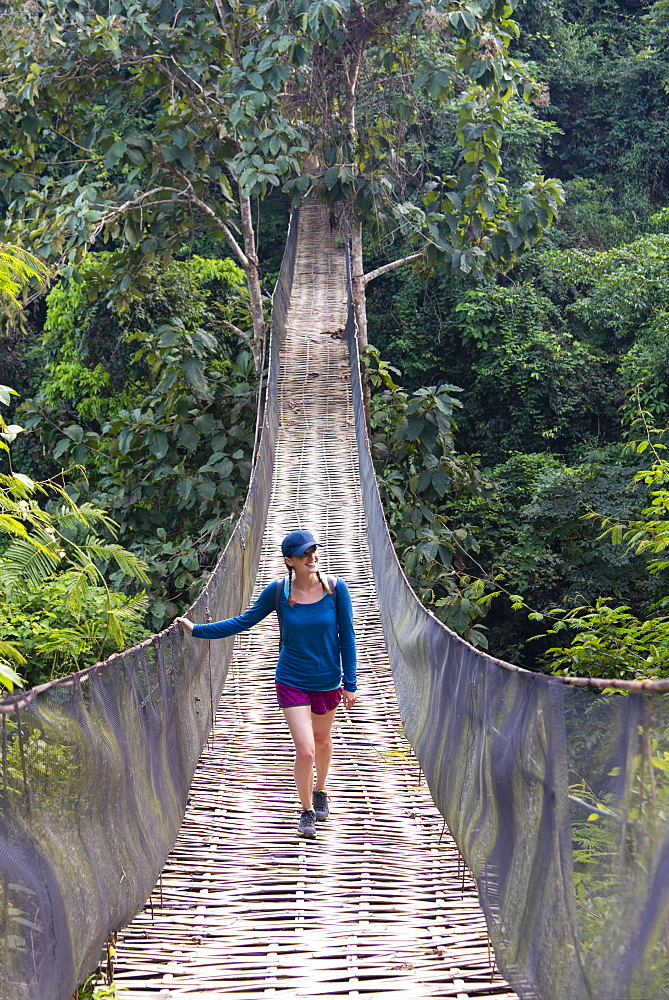 A woman crosses a precarious looking suspension bridge over the jungle in Laos. - 1315-337