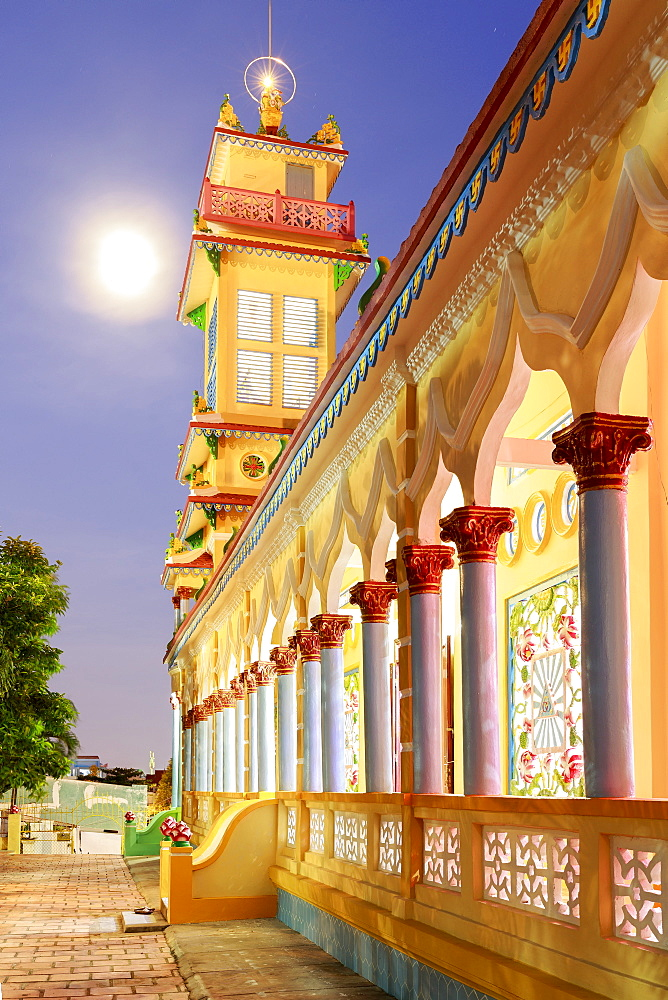 The Cao Dai temple in Vung Tau lit up at dusk with the full moon to the left of the tower, Vung Tau, Vietnam, Indochina, Southeast Asia, Asia - 1317-10