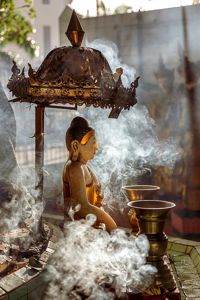 A small Buddha statue at Sule pagoda, surrounded by clouds of smoke with two Kinaree statues visible in the background, Yangon (Rangoon), Myanmar (Burma), Asia