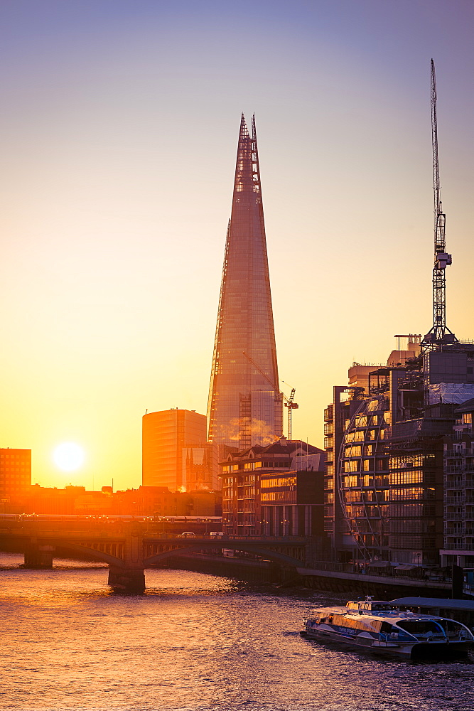 The Shard at sunrise on a cold winters morning with River Thames and river cruise boat and sun reflections in windows, London, England, United Kingdom, Europe