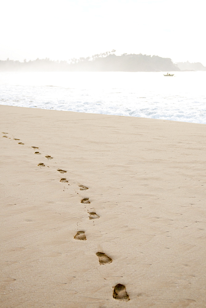 Footprints in the sand at sunrise on Talalla Beach, Sri Lanka, Asia