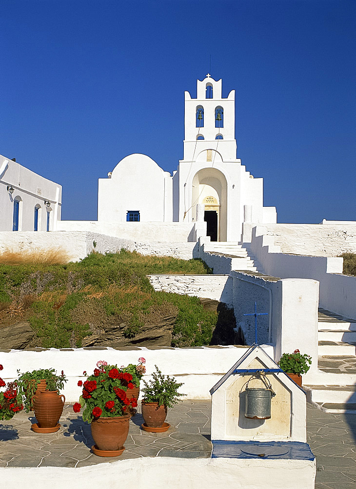 Pots of geraniums beside a well in front of the white walls and bell tower of the Monastery of Panagia Chrysopigi on Sifnos, Cyclades, Greek Islands, Greece, Europe