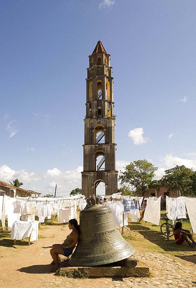 Hand crafted linens for sale beside the Manaca Iznaga Estate Tower and a bell which used to be rung to announce work hours for slaves on the plantation, Valle de los Ingenios, Eastern Cuba, Cuba, West Indies, Central America