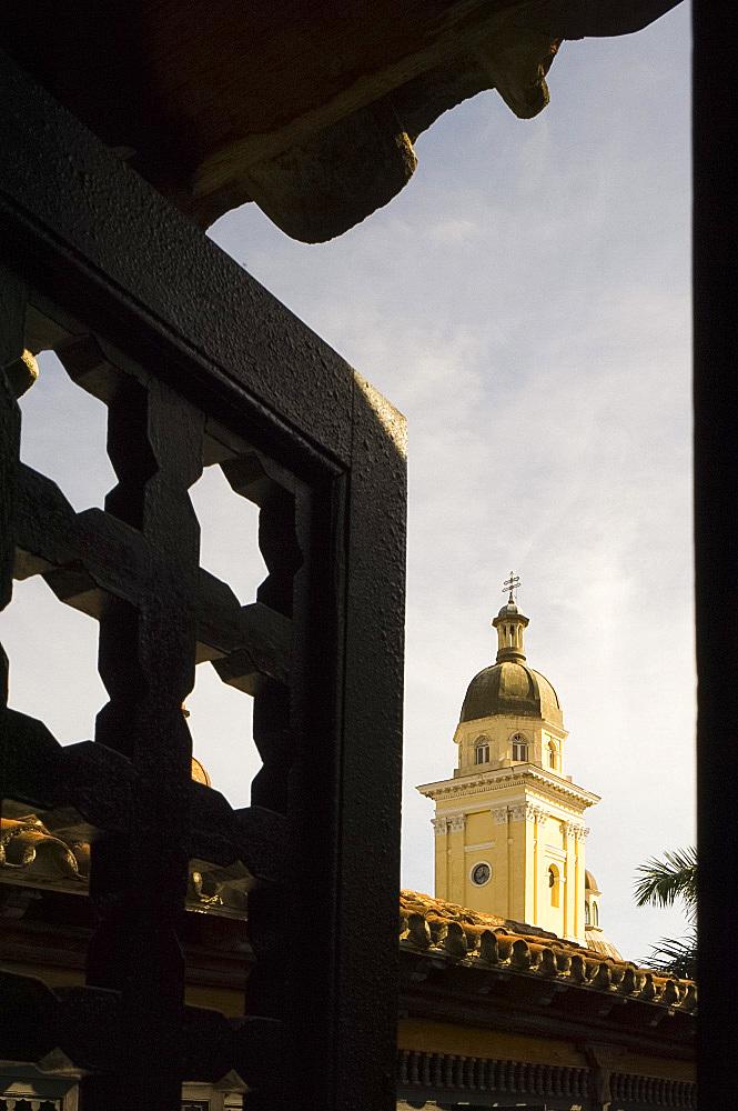 The belltower of Catedral de la Anuncion seen through the wooden screens of Casa de Diego Velazquez, Santiago de Cuba, Cuba, West Indies, Central America