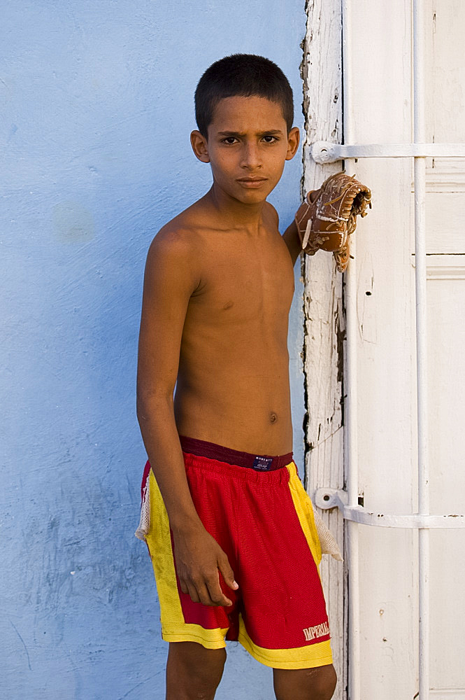 A young Cuban boy with a baseball mitt in Trinidad, Cuba, West Indies, Central America