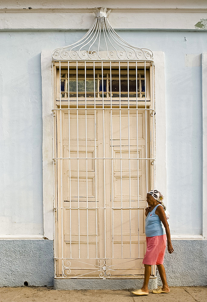 A woman walking past a typical door with ornate iron bars, Trinidad, Cuba, West Indies, Central America