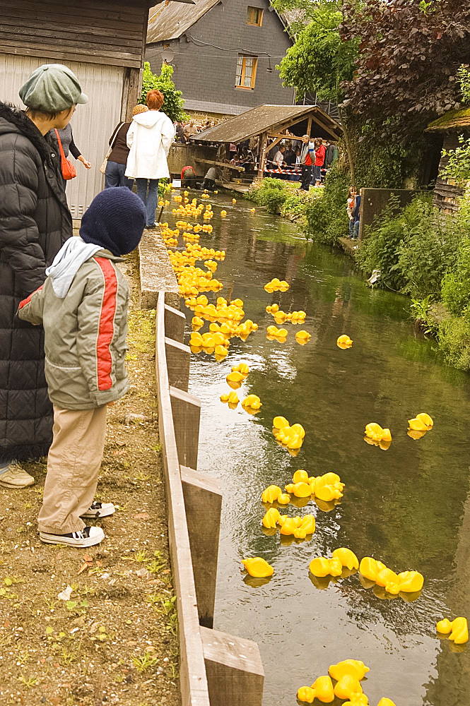 People watching the traditional rubber duck race along a stream in Cormeilles, Normandy, France, Europe