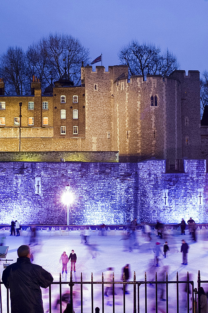 Skaters on the ice rink next to The Tower of London at dusk, London, United Kingdom, Europe