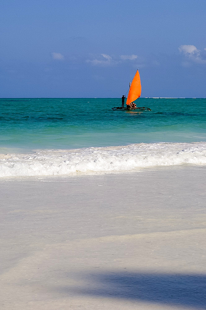 A traditional wooden dhow with an orange sail in the Indian Ocean, Paje, Zanzibar, Tanzania, East Africa, Africa