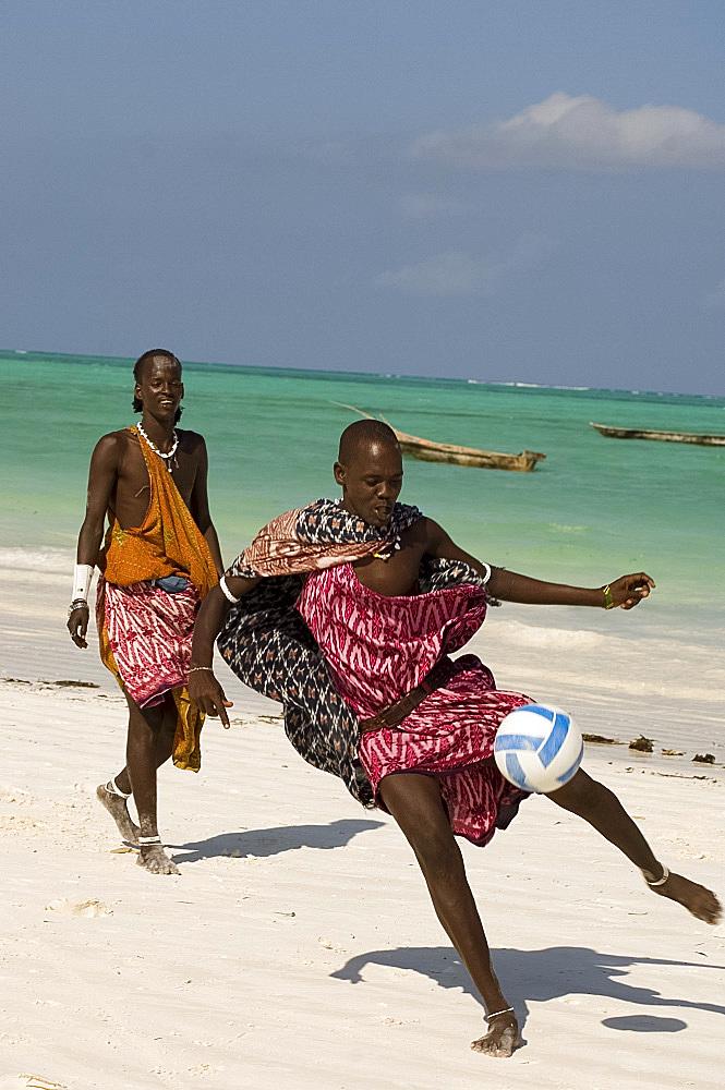 Maasai tribesmen in colourful native dress playing football on the beach, Paje, Zanzibar, Tanzania, East Africa, Africa