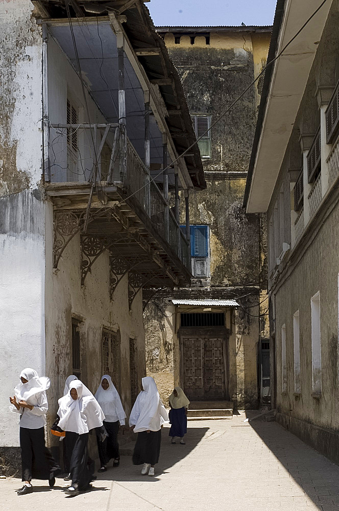 Schoolgirls in white headscarves walking in Stone Town, Zanzibar, Tanzania, East Africa, Africa